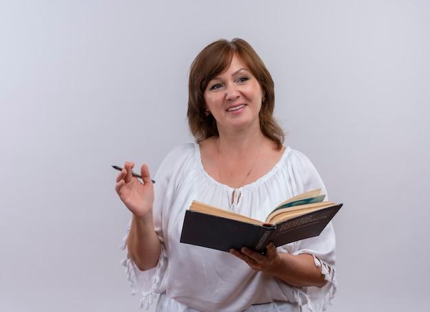Sorridente donna di mezza età tenendo il libro e la penna sul muro bianco isolato