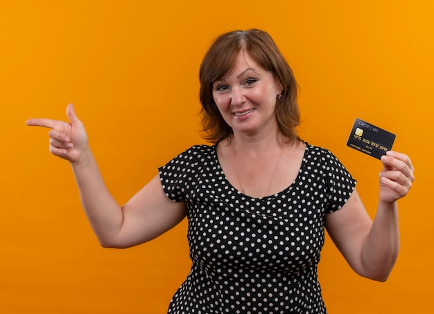 カードを保持している孤立したオレンジ色の壁の左側にある指で指している中年の女性の笑顔