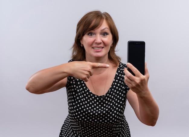 Улыбающаяся женщина средних лет держит мобильный телефон и показывает на него пальцем на изолированной белой стене