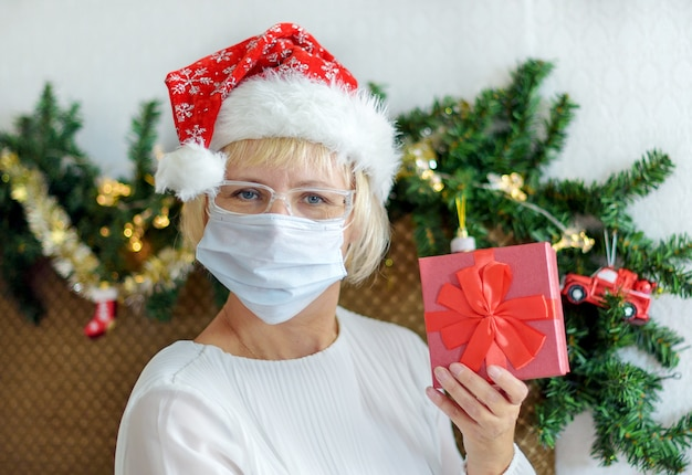 의료 마스크와 산타 모자에 중간-세 여자를 웃 고. 크리스마스를 축하합니다.