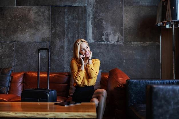 高級ホテルのロビーに座って電話で会話し、ホテルにチェックインするのを待っているスーツを着た中年女性の笑顔。