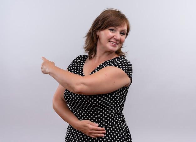 中年の女性の後ろに指で指していると分離の白い壁の腹に手を入れて笑顔