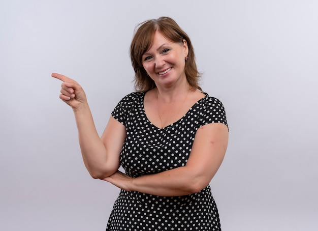 Smiling middle-aged woman pointing with finger at left side on isolated white wall