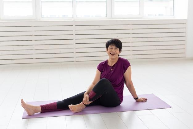 운동 매트에 앉아 웃는 중년 여성