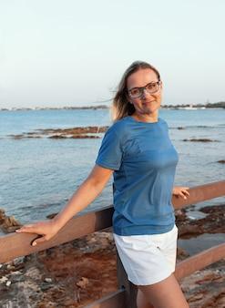Улыбающаяся женщина средних лет в синей футболке и очках, стоящая на закате на деревянном мосту с рукой на нем. макет футболки