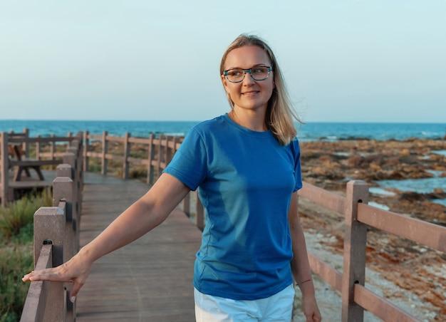 Улыбающаяся женщина средних лет в синей футболке и очках стоит на закате на деревянном мосту с рукой на нем. макет футболки