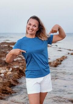 Улыбающаяся женщина средних лет в синей футболке, указывая на нее и стоя на скале на закате. макет футболки