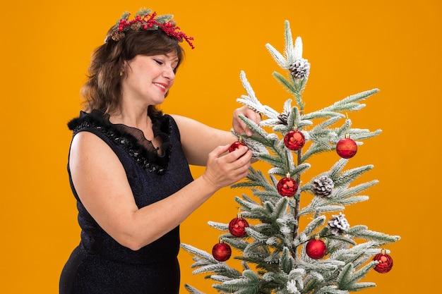 프로필보기에서 크리스마스 트리 근처에 서있는 목 주위에 크리스마스 머리 화환과 반짝이 갈 랜드를 입고 웃는 중년 여성