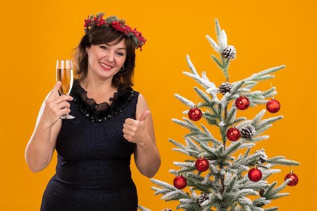 샴페인 잔을 들고 장식 된 크리스마스 트리 근처에 서있는 목 주위에 크리스마스 머리 화환과 반짝이 갈 랜드를 입고 웃는 중년 여성