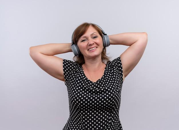 ヘッドフォンを着用し、孤立した白い壁に頭の後ろに彼女の手を置く中年の女性の笑顔
