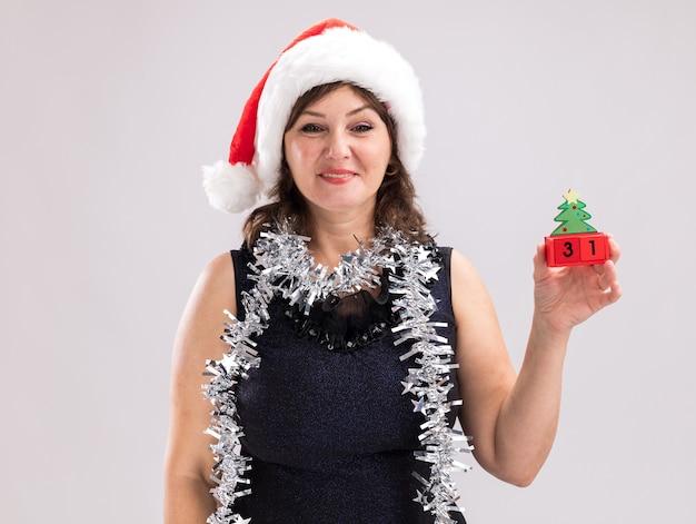 Улыбающаяся женщина средних лет в новогодней шапке и мишурной гирлянде на шее держит елочную игрушку с датой, глядя в камеру, изолированную на белом фоне