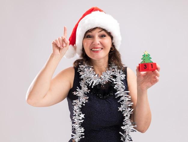 サンタの帽子と見掛け倒しの花輪を首に身に着けている中年の女性の笑顔は、白い背景で隔離のカメラを上向きに見ている日付とクリスマスツリーのおもちゃを保持しています