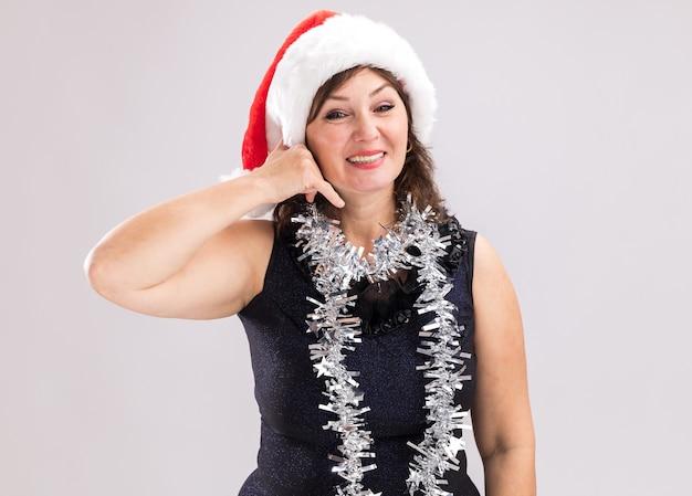 Улыбающаяся женщина средних лет в новогодней шапке и мишурной гирлянде на шее, глядя в камеру, делает жест вызова на белом фоне