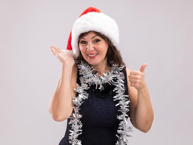 흰색 배경에 고립 된 빈 손과 엄지 손가락을 보여주는 카메라를보고 목에 산타 모자와 반짝이 갈 랜드를 입고 웃는 중년 여성