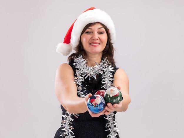 コピースペースで白い背景で隔離のカメラを見てカメラに向かってクリスマスつまらないものを伸ばして首の周りにサンタの帽子と見掛け倒しの花輪を身に着けている中年女性の笑顔
