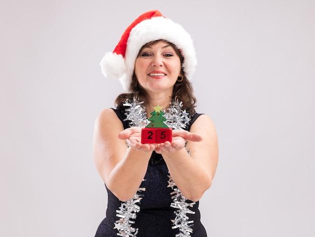 복사 공간이 흰색 배경에 고립 된 카메라를보고 카메라를 향해 날짜와 함께 크리스마스 트리 장난감을 뻗어 목 주위에 산타 모자와 반짝이 갈 랜드를 입고 웃는 중년 여성