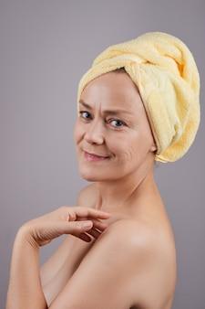 灰色の壁のプロファイルで、彼女の肌にクリームを適用する裸の肩を持つ笑顔の中年女性。フェイシャルスキンケアのコンセプト。