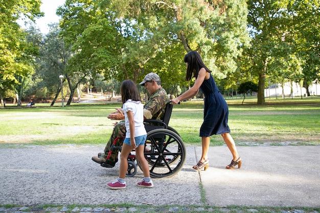 Militare sorridente che cammina con la famiglia nel parco cittadino. madre dai capelli lunghi che spinge la sedia a rotelle. bambina che cammina e parla con papà disabile. famiglia all'aperto, weekend e concetto di disabilità
