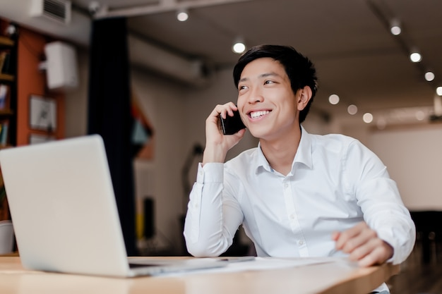 Smiling millenial asian businessman talking on the phone in the company office with laptop