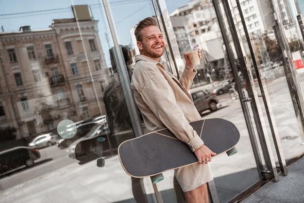 Улыбающийся тысячелетний белокурый парень, держащий на вынос чашку кофе с капучино, стоя на городской улице стеклянное здание фон битник скейтбордист, держащий longboard. концепция экстремального отдыха. городские привычки.