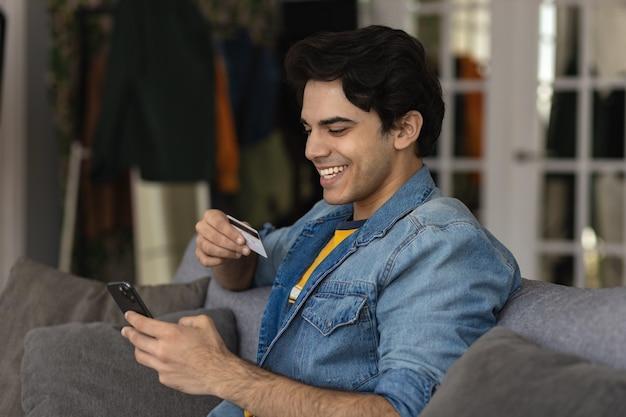 遠くにお金を払うためにプラスチックのクレジットカードとスマートフォンを手に持っている千年紀の白人男性の笑顔、オンラインショッピング、eバンキングサービスを介したオンラインでの安全な支払い