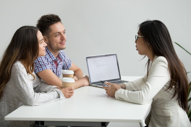Smiling millennial couple listening to asian advisor lawyer consulting customers