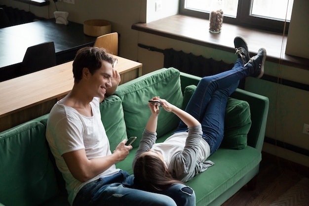 Smiling millennial couple talking holding smartphones relaxing on couch together