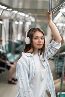 地下鉄の電車の中でワイヤレスイヤホンで音楽を聴いているミレニアル世代のかわいい女の子の乗客の笑顔