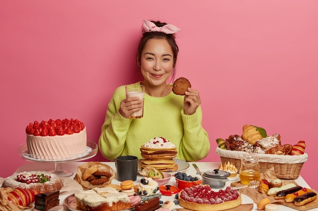 Sorridente ragazza millenaria indossa fascia, maglione verde, beve latte e mangia biscotti d'avena, ha comprato varie torte, un tavolo pieno di gustosi dessert