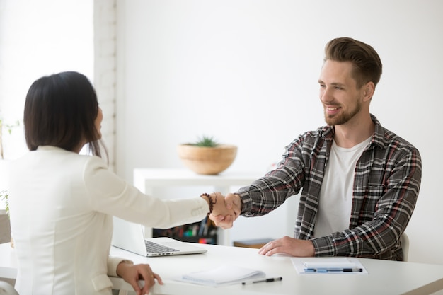 Smiling millennial partners handshaking in office thanking for successful teamwork
