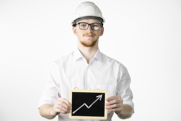 Smiling mining engineer looks at camera holding sign with up arrow