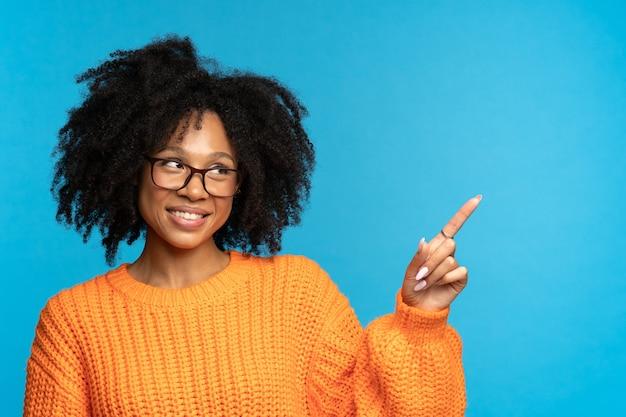 안경을 쓴 웃고 있는 혼혈 여성이 제품 온라인 과정이나 서비스를 위한 빈 공간을 손가락으로 가리킵니다.