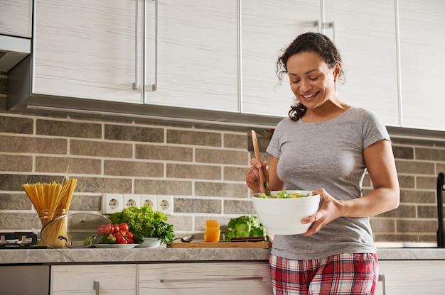부엌에서 웃 고있는 동안 나무로되는 숟가락으로 야채 샐러드를 저 어 혼합 된 국적 여자 웃 고. 가정 생활과 건강한 식생활 개념
