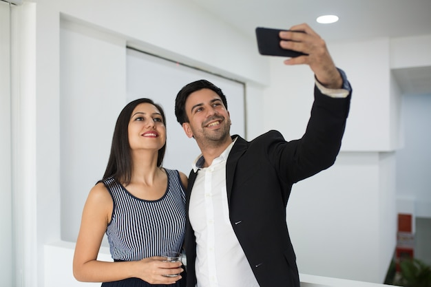 Smiling mixed race businessman photographing with colleague