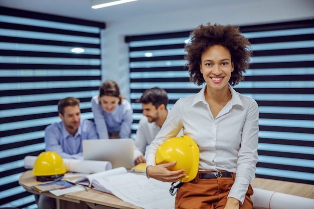 Smiling mixed race female architect sitting on the desk in office and holding helmet in her hands