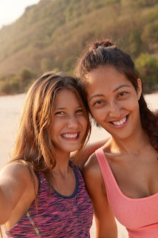 Smiling mixed race female friends pose near for making selfie, dressed in top