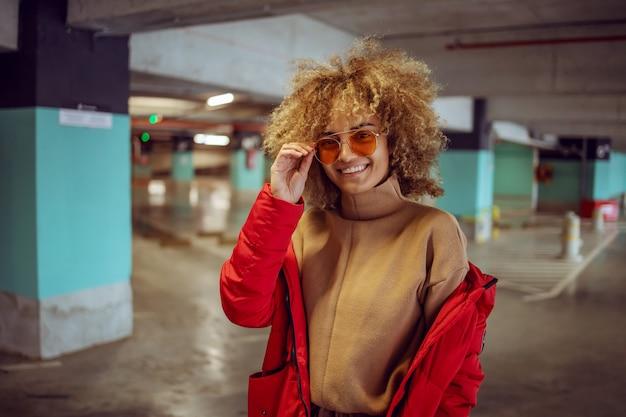 Улыбающаяся хип-хоп девушка смешанной расы в куртке стоит в гараже и поправляет солнцезащитные очки