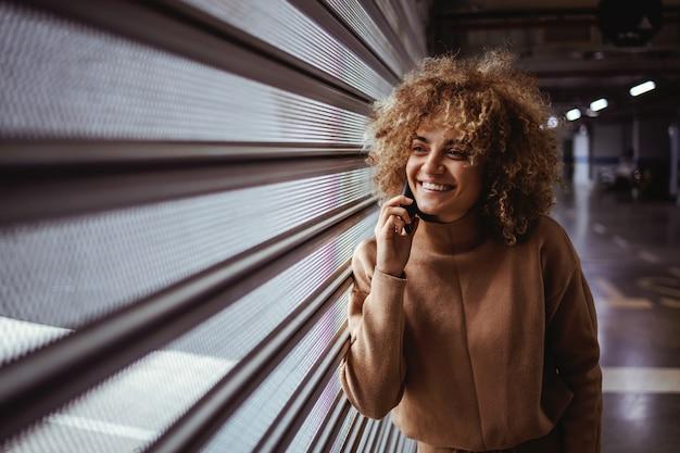 ガレージのドアに寄りかかって電話で会話している混血ヒップホップの女の子を笑顔。
