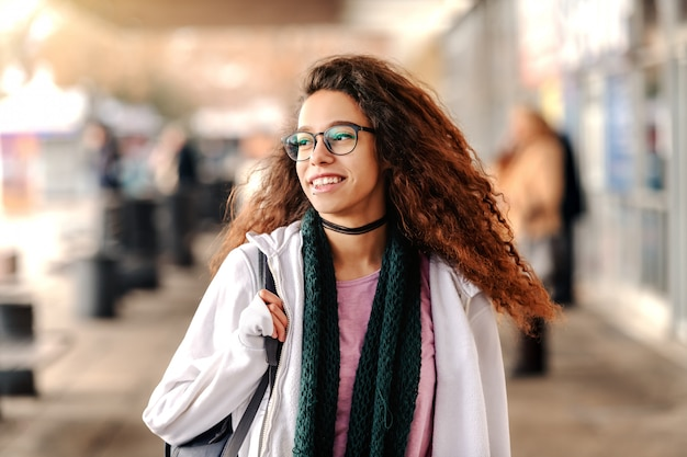 Smiling mixed race hipster girl standing at train station and looking away.