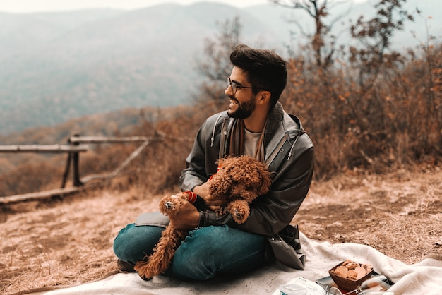 Smiling mixed race man in raincoat holding poodle in his lap while sitting on the blanket in nature at autumn.
