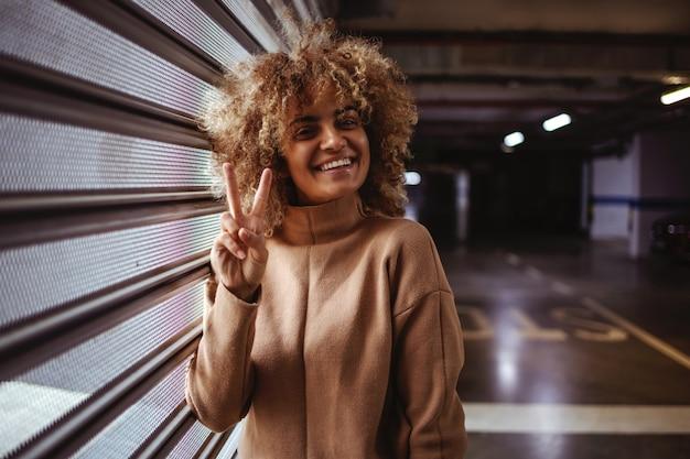 Улыбающаяся рэп-девушка смешанной расы, опираясь на дверь гаража и показывая жест победы.