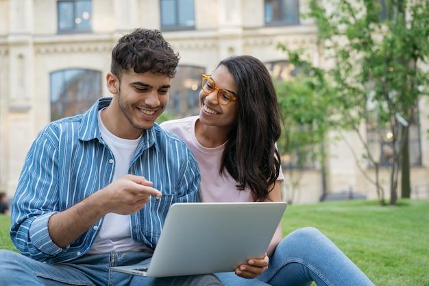 Улыбающиеся студенты смешанной расы, использующие ноутбук, вместе учатся в концепции онлайн-образования в парке