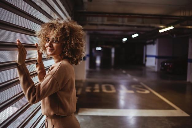ガレージのドアの横に立っている笑顔の混血トラップの女の子