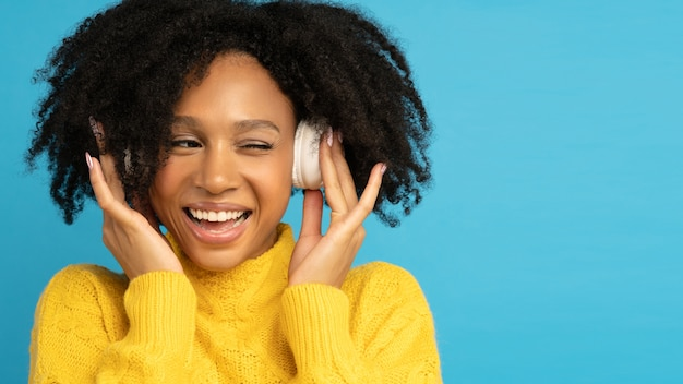 Smiling mixed race woman touching wireless headphones, listening to music, winks and looks away