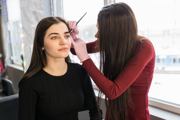 Улыбающаяся модель делает процедуру покраски бровей