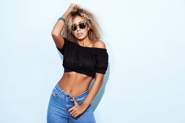 Smiling model woman in trendy jeans and sunglasses posing