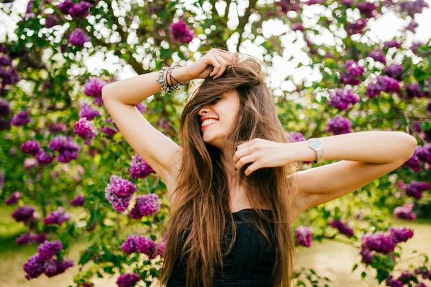 夏のライラックガーデンで長い髪のモデルの女性の笑顔