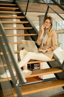 Улыбается современная деловая женщина сидит на лестнице в офисе, работает на ноутбуке и разговаривает по мобильному телефону