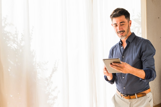 Smiling modern man standing in front of white curtain using digital tablet