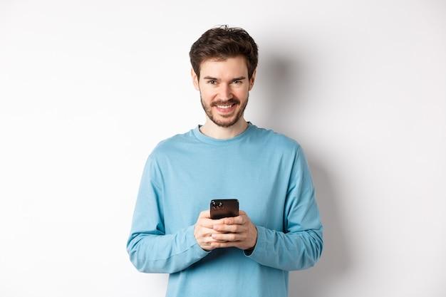 스마트 폰을 사용하고 카메라를 기쁘게 찾고 현대인 미소. 흰색 바탕에 휴대 전화와 운동복에 남자.
